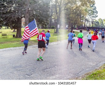 MONTGOMERY, ALABAMA - MARCH 10, 2018:  2018 Montgomery Half Marathon and 5k:  Mature Marine bears the United States Flag to honor a fallen soldier shown on tee shirt back as he hits the halfway mark.