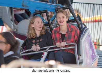 Montgomery, Alabama, USA - October 29, 2017: Two caucasian blond girls laughing and smiling on an amusment ride at the Alabama National Fair.