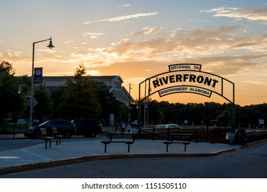 Montgomery, Alabama/USA-June 27, 2018: The sign leading to the tunnel to the Riverfront in Montgomery with the Trainshed and a sunset sky in the background.