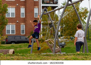 Montgomery County, MD, USA 09/26/2020: An African American and a caucasian boy are playing together in the local playground in their suburb neighborhood. One of them jumps off the swing for fun.