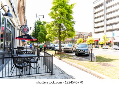 Montgomery, USA - April 21, 2018: Road street during day in capital Alabama city, cars parked in downtown old town by the alley historic shops, Jimmy John's restaurant, JJ gourmet sandwiches