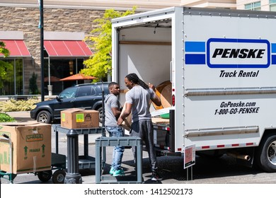 Montgomery, USA - April 21, 2018: Town in Alabama street neighborhood with city sidewalk and people moving movers men packing boxes in Penske truck