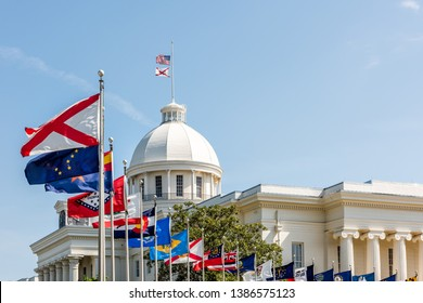 Montgomery, USA State capitol building in Alabama during sunny day with old historic architecture of government and many row of flags by dome