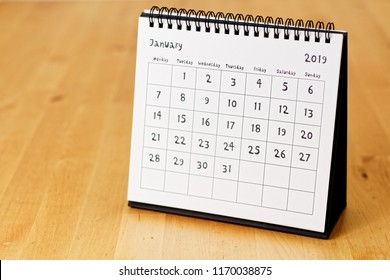 Month page: January in 2019 paper calendar with funny font on the wooden table