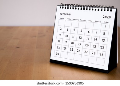 Month page: November in 2020 paper calendar with funny font on the wooden table