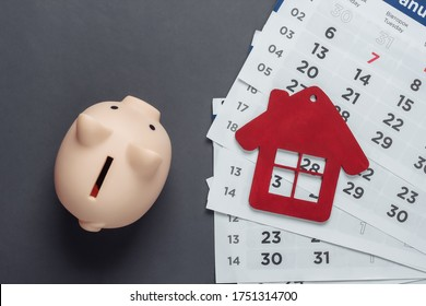 Monthly Budget. Paying rents for housing. Piggy bank, house figurine with monthly calendar on gray background. Top view