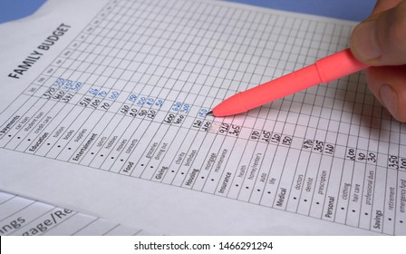 Monthly Family Budget Worksheet. Household accounting on the paper. Calculating monthly income expenses payments cost spending and savings. Woman analyze family budget at home