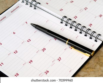 monthly planner with pen on the table
