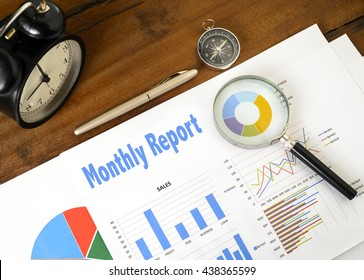 """""""Monthly Report"""" text on paper sheet with magnifying glass on chart clock,compass, pen, on wooden table - business, banking, finance and investment concept"""