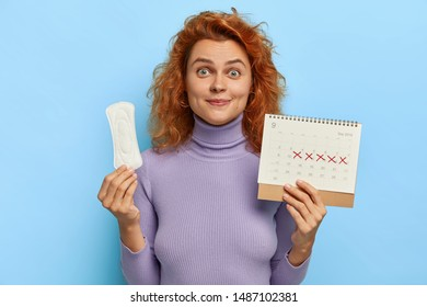 Monthly woman menstruation control concept. Lovely ginger young woman holds clean sanitary napkin pad periods calendar uses feminine intimate product during menses or critical days. Hygiene protection