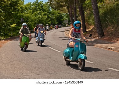 Montiano, FC, Italy - May 25, 2014: girl leads a group of bikers riding a vintage italian scooter Vespa on the countryside during the motorcycle rally Vespagiro