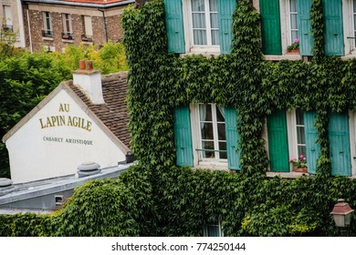 Montmartre houses grown with ivy plant. On the left famous historical building od The Agile Rabbit - a cabaret artistique, small bar-bistro. Paris France 2013 July 03