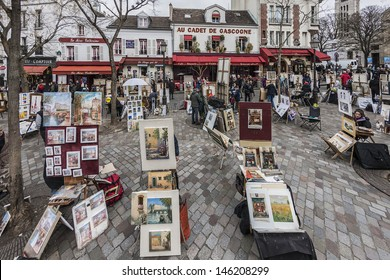 MONTMARTRE - MARCH 13: Artists easels and artwork set up in Place du Tertre in Montmartre, Paris on March 13, 2012. Montmartre attracted many famous modern painters in the early 20th century.