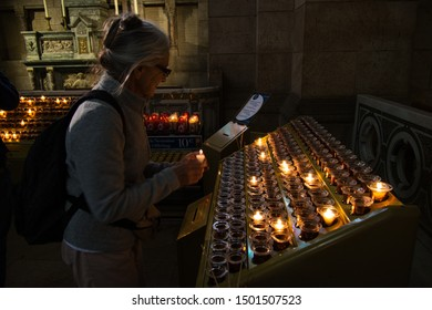 Montmartre, Paris, France - 09/02/2019: Lighting a prayer candle in St Peter's church