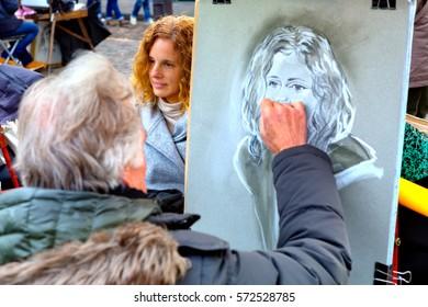 Montmartre, Paris, France - 12.10.2016: painter drawing a portrait of a young woman on Place du Tertre on Montmartre district in Paris, France