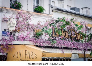 Montmartre, Paris / France - 4 August 2018: A picture of the facade of Le Vrai Paris cafe in Montmartre that has beautiful pink flowers growing around it.