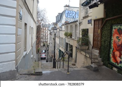 MONTMARTRE, PARIS/FRANCE - DECEMBER 2017: Street and stairs of Montmartre with graffiti, buildings and trees. Paris/France.