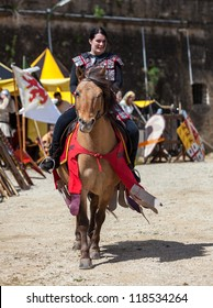 MONTMEDY,FRANCE,APRIL 29:Unidentified medieval woman riding a horse in a traditional tournament during a reenactment medieval festival on April 29 2012 in Montmedy, France.