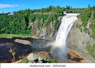 Montmorency Falls with rainbow and blue sky near Quebec City.