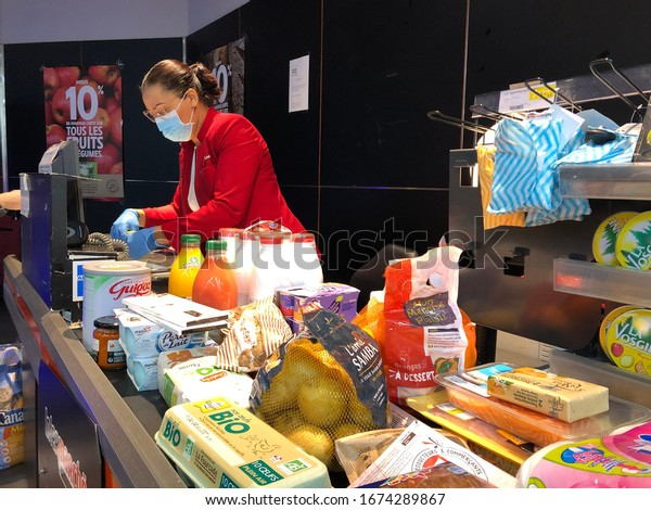 Montpellier, Occitanie, France - 03 16 2020: Hero cashier with a mask working hard to answer people's panic demand, stores are filled with crowds in the lockdown of the coronavirus covid-19 pandemic