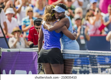 MONTREAL - AUGUST 9: Venus Williams of USA hugs her sister Serena Williams of USA after her semi final win at the 2014 Rogers Cup on August 9, 2014 in Montreal, Canada.
