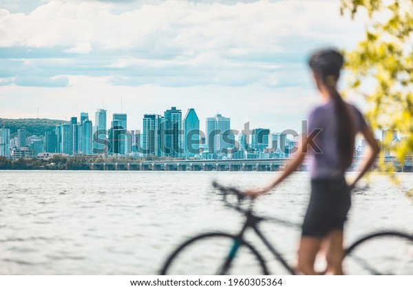 Montreal biking woman cyclist with bike looking at skyline view of condo towers and buildings downtown against Mount Royal landscape. Summer outdoor cycling sport active lifestyle.