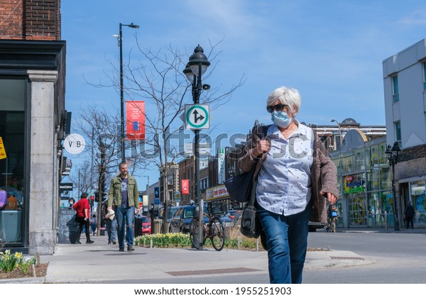 Montreal, CA - 11 April 2021: Pedestrian with face mask for protection from COVID-19 walking down the street