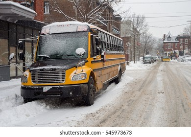 Montreal, CA - 12 December 2016: Yellow school bus parked in Mile End neighborhood during Snowstorm