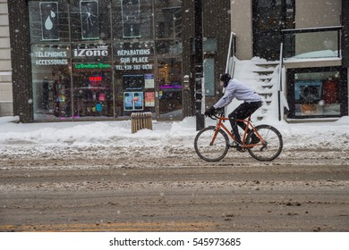 Montreal, CA, 12 December 2016. Man riding bike in Mile End neighborhood during snow storm