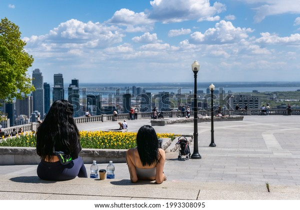 Montreal, CA - 14 May 2021: People enjoying view of Montreal skyline from Kondiaronk Belvedere located at the top of the Mont-Royal mountain.