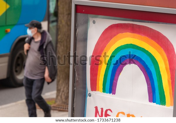 Montreal, CA - 16 May 2020: Man with face mask for protection from COVID-19 walking near rainbow drawing