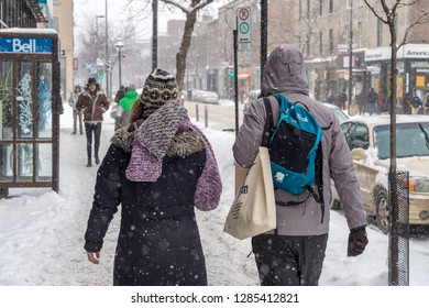 Montreal, CA - 17 December 2016: Snow storm in Montreal. Pedestrians on Mont-Royal Avenue.