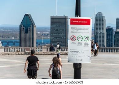 Montreal, CA - 18 May 2020 : Sign showing french Covid-19 safety guidelines and Montreal skyline in the distance.