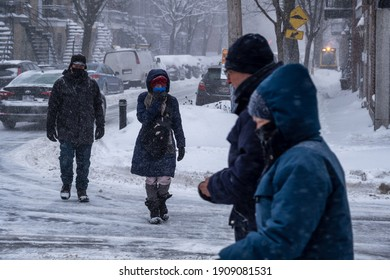 Montreal, CA - 2 February 2021: People with protective face masks walking on the street during heavy snowfall