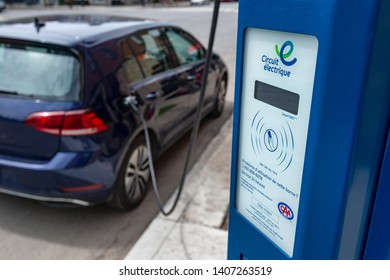 Montreal, CA - 25 May 2019: Electric car plugged into an EV charging station.