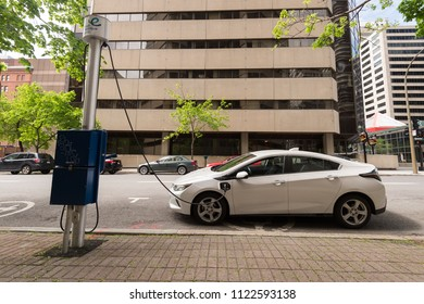 Montreal, CA - 27 May 2017: Chevrolet Volt electric car plugged into an EV charging station in Downtown Montreal