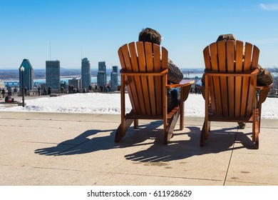 Montreal, CA - 30 March 2017: People sitting on a wooden lawn chair and enjoying a sunny spring day on Kondiaronk Belvedere