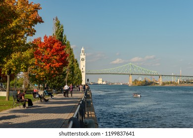 Montreal, CA - 9 October 2018: Montreal Clock Tower and Jacques Cartier Bridge with autumn colours