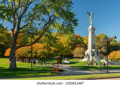 Montreal, Canada - 14 October 2018: Mont-Royal foliage bursts with autumn colors, as people are standing next to George-Etienne Cartier Monument.