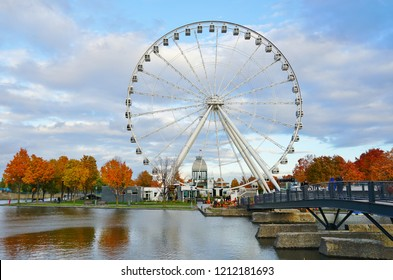 MONTREAL, CANADA -17 OCT 2018- View of the Grande de Roue de Montreal giant observation Ferris Wheel in the fall with autumn foliage located on the Vieux Port de Montreal harbor in Quebec, Canada.