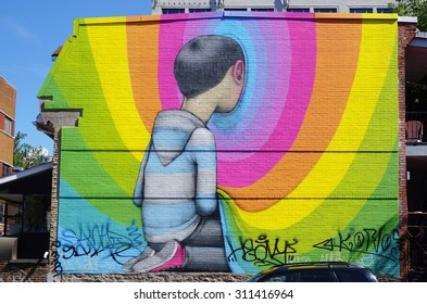 MONTREAL, CANADA -18 AUGUST 2015- Rainbow colored street art wall mural by French graffiti muralist Seth Globepainter in Montreal near Boulevard Saint-Laurent.