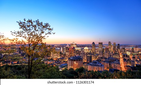 Montreal, CANADA, 21 May 2018. Montreal sunrise view from Belvedere with summer colorful leaves. Beautiful panorama of Montreal downtown skyline in summer night time.