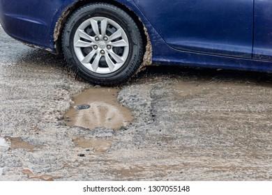 Montreal, Canada - 7 February 2019: Car driving through a pothole.
