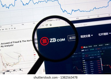 MONTREAL, CANADA - APRIL 26, 2019: ZB.com cryptocurrency digital assets exchange logo and home page on a laptop screen under magnifying glass.