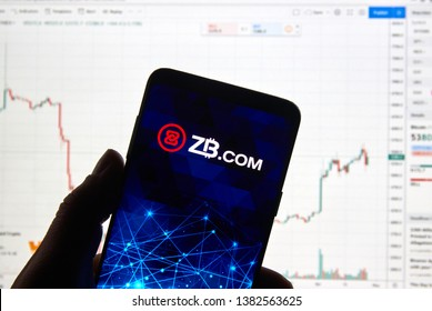 MONTREAL, CANADA - APRIL 26, 2019: ZB.com cryptocurrency exchange logo and application on Android Samsung Galaxy s9 Plus screen in a hand over a laptop display with bitcoin chart on it.