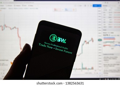 MONTREAL, CANADA - APRIL 26, 2019: BW.com cryptocurrency exchange logo and application on Android Samsung Galaxy s9 Plus screen in a hand over a laptop display with bitcoin chart on it.