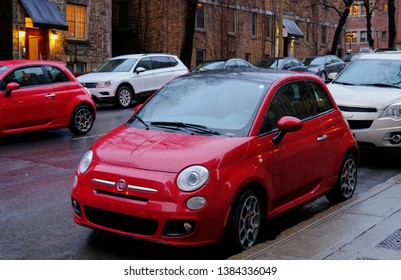 Montreal, Canada - April 26, 2019: FIAT 500 red little car passes by another. The distinct retro style is based on 1957 original model which considered as one of the first purpose-built city cars.