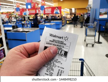MONTREAL, CANADA - APRIL 30, 2019: A hand holding a Walmart receipt in Walmart store. Walmart is an American retail corporation that operates a chain of hypermarkets and discount department store