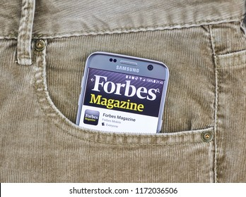 MONTREAL, CANADA - AUGUST 10, 2018: Forbes app on a cellphone screen in a jeans pocket. Forbes is an American family-controlled business magazine with articles on finance, industry, investing