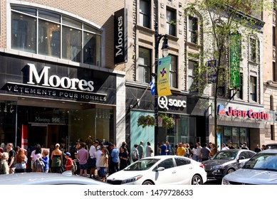 Montreal, Canada - August 10, 2019:  A big crowd of people stand in line for the Quebec Cannabis Corporation (SDQC) store on Saint-Catherine St. The sale of recreational cannabis is legal in Canada